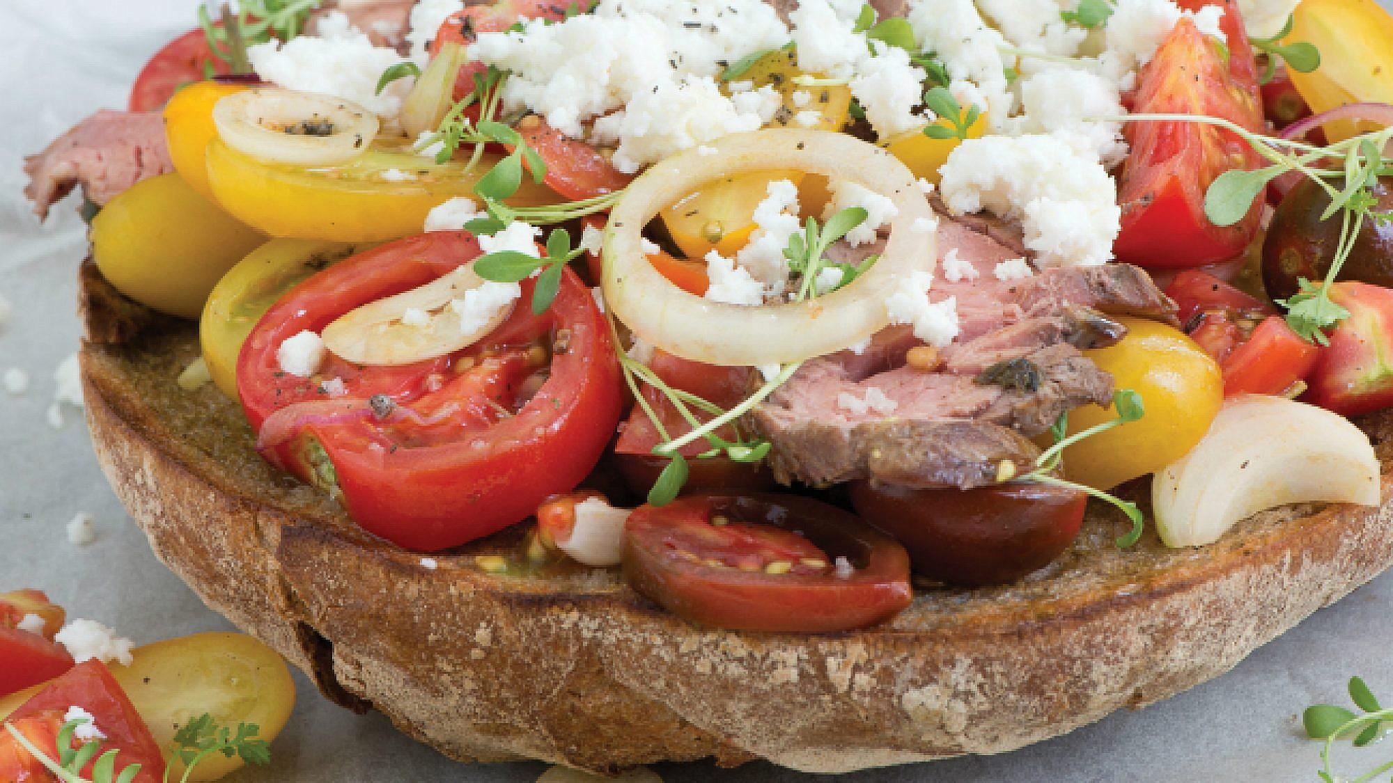 ברוסקטה ענקית עם רוסט פילה, סלט עגבניות צבעוניות וגבינה צ'רקסית. צילום: עודד מרום | סגנון : אוריה גבע