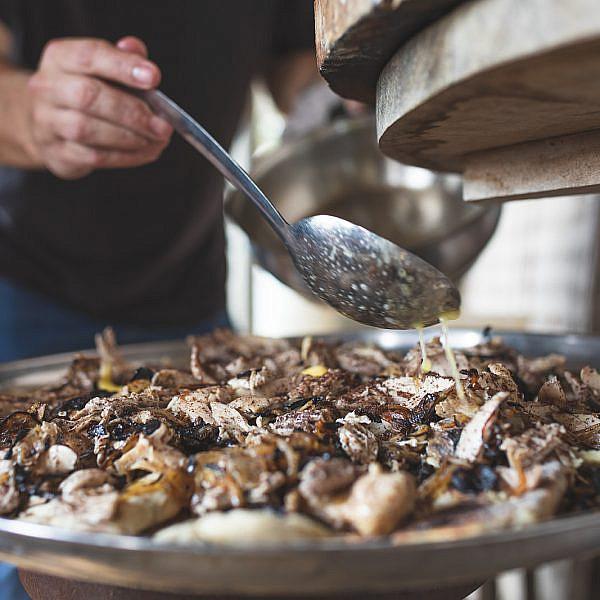 עוף מפורק על לחם נאן ובצל מטוגן של  עינב אזגורי. צילום: שני בריל