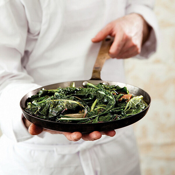 סלט חם של עלי חורף של שף יהונתן בורוביץ'. צילום: דניה ויינר | סגנון: אוריה גבע