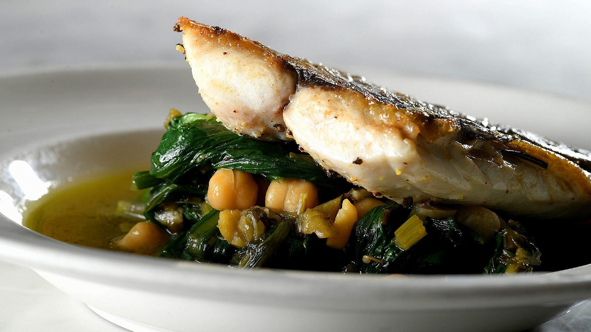 תבשיל עלים ירוקים עם חומוס ודג צלוי של שף עינב אזגורי. צילום: רן בירן