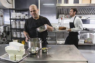 שף עינב אזגורי ושף־קונדיטור שגיא מלר מכינים את עוגת הגבינה הבאסקית של קפה נורדוי. צילום: אנטולי מיכאלו
