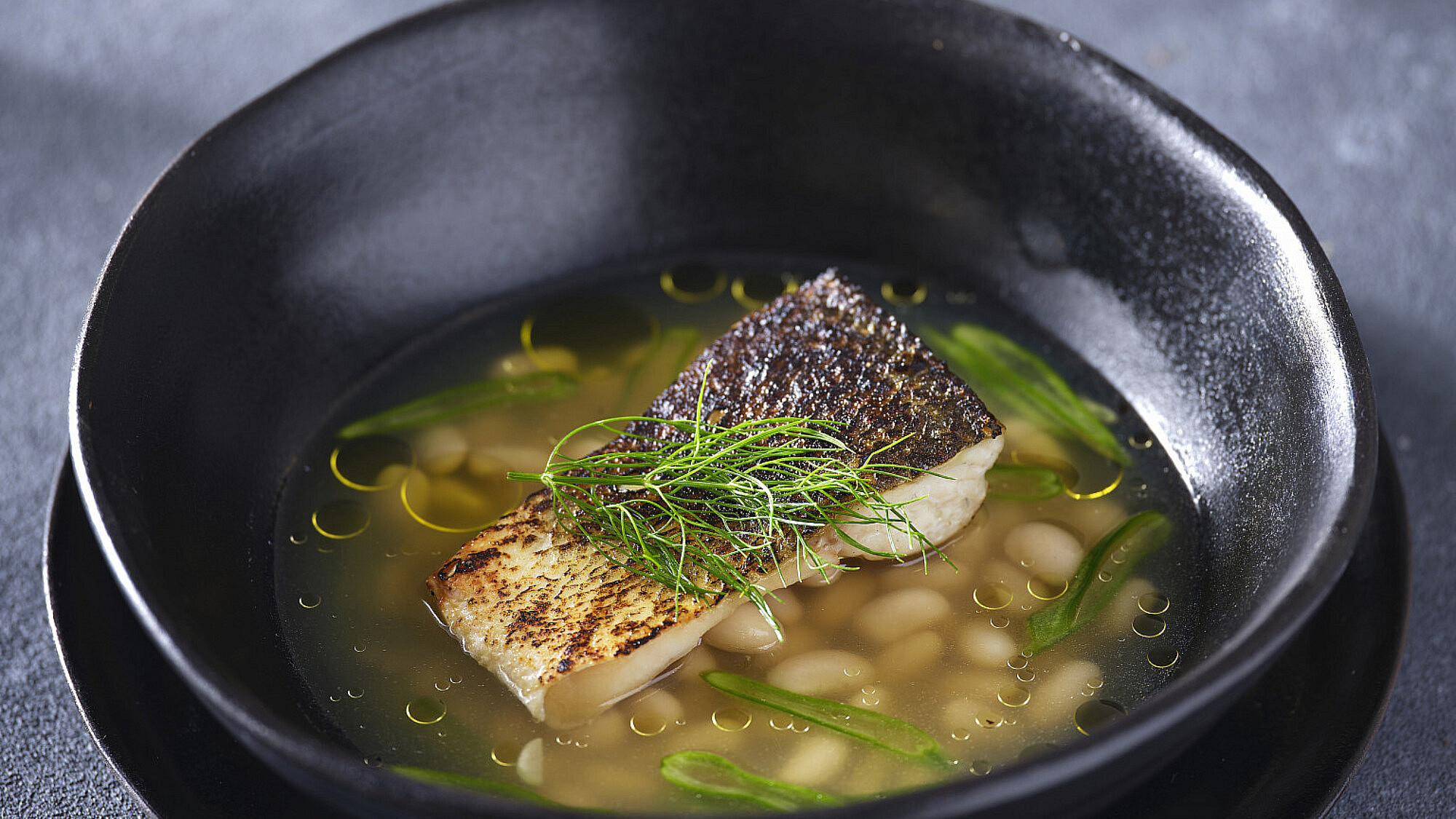 דג בגריל, בציר עצמות מעושנות ושעועית של גל בן משה. צילום: אנטולי מיכאלו. כלים: סטודיו עדי ניסני.